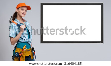 female manual worker and blank computer monitor with copy space - stock photo