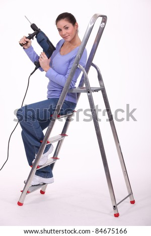 Female manual worker with drill and ladder