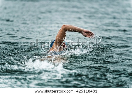 Female marathon swimmer in action. Photo taken from trailing boat. High speed action shot, focus on swimmer, shallow depth of field - stock photo