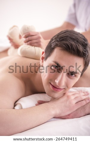 Female masseur doing massage on male body with spa herbal balls in the spa salon.