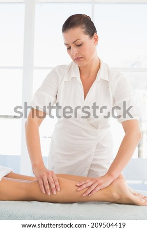 Female masseur massaging woman's leg at spa center