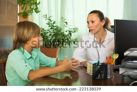 Female mature doctor examining teenage boy in office. Focus on woman  - stock photo