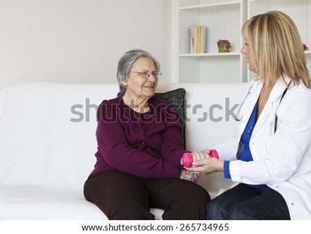 Female mature nurse visit a senior woman at home. They sitting on the sofa in the living room and senior woman  lifts dumbbells with female nurse. - stock photo