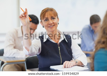 Female mature student raising her hand while sitting in classroom - stock photo