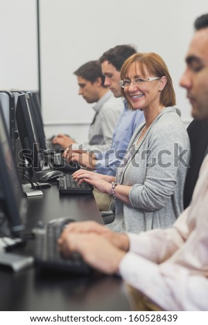 Female mature student sitting in computer class smiling at camera - stock photo