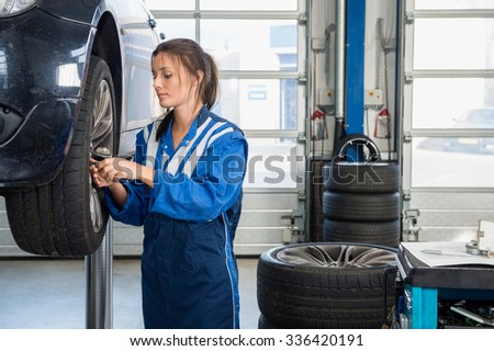Female mechanic changing tire from suspended car at auto shop - stock photo