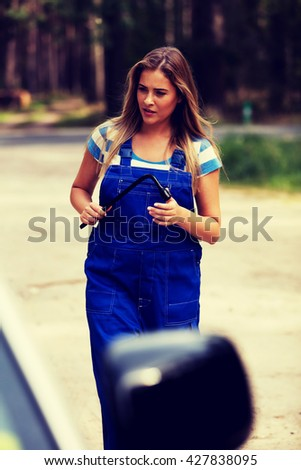 Female mechanic changing tire with wheel wrench - stock photo