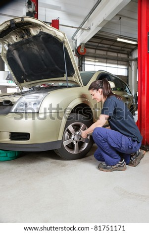Female mechanic changing wheel of car with pneumatic torque wrench - stock photo