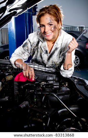 Female mechanic fixing a car at the garage - stock photo