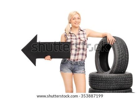 Female mechanic holding a big black arrow pointing left and leaning on a stack of car tires isolated on white background - stock photo