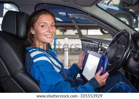 Female mechanic, running a diagnostics program, connected to the computer of the cars, sitting in the drivers seat using a sturdy touch screen terminal - stock photo