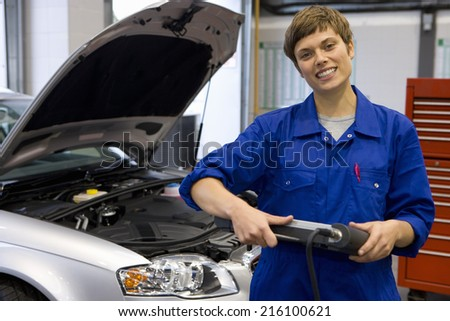 Female mechanic with electronic diagnostics device, portrait