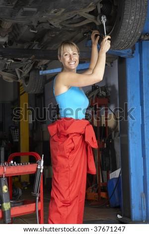 Female mechanic working on car - stock photo