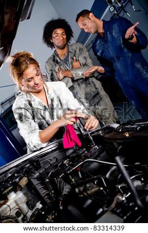 Female mechanic working on the hood of a car while colleagues watch - stock photo