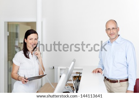 Female medical assistant answers phone call at reception while patient is waiting - stock photo