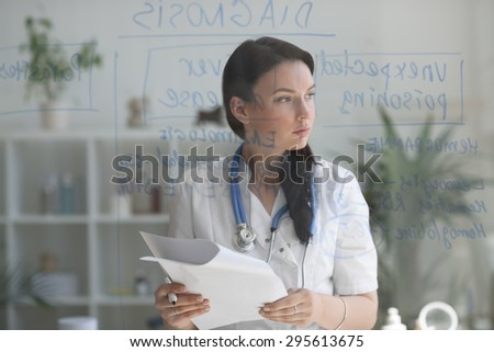 Female medical doctor working at clinic office. Writing on glass whiteboard symptoms and test results of her patient to diagnose disease - stock photo