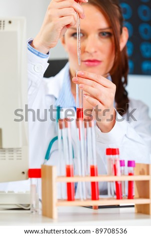 Female medical doctor working with test tube at cabinet - stock photo
