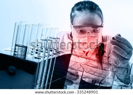 female medical or scientific researcher or woman doctor looking at a test tube of clear solution in a laboratory - stock photo