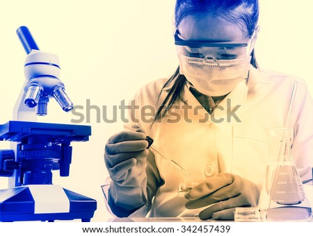 female medical or scientific researcher or woman doctor looking at a test tube of clear solution in a laboratory with her microscope beside her - stock photo