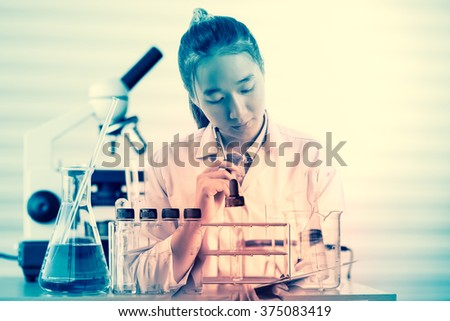 female medical or scientific researcher or woman doctor thinking for write report in a laboratory with her microscope beside her - stock photo