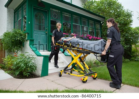 Female medical team taking elderly woman to hospital - stock photo
