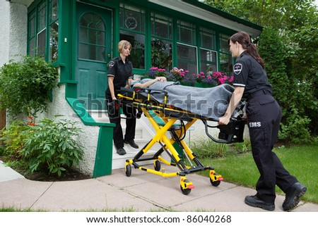 Female medical team wtih patient on stretcher - stock photo