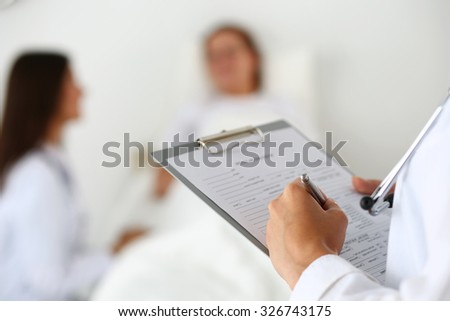 Female medicine doctor filling in patient medical history list during ward round while patient communicating with doctor. Medical care or insurance concept. Physician ready to examine and help - stock photo