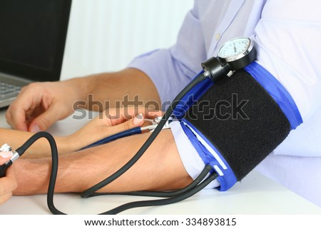 Female medicine doctor measuring blood pressure to her patient. Hands close up. Medical and healthcare concept - stock photo