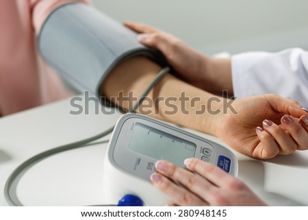 Female medicine doctor measuring blood pressure to patient. Patient communicates with physician doctor having medical examination. Medical concept. Hand of doctor and patient while pressure measuring - stock photo