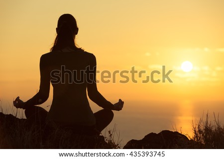 Female meditating overlooking the beautiful sunset. Healthy mind body and spirit concept.  - stock photo