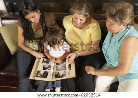 Female members of a family looking at a photo album together - stock photo