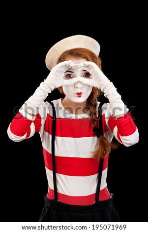 Female MIM comedian depicts that looks into the distance,  isolated on black  background.Studio shot. - stock photo