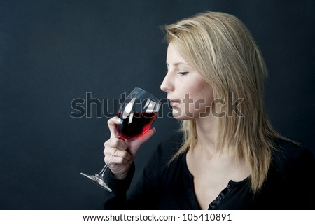 female model holding wineglass full of red wine - stock photo