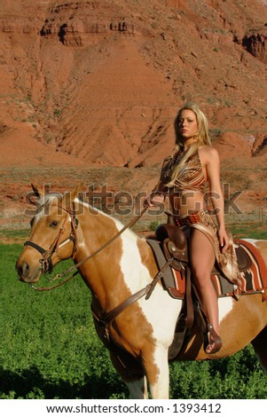 female model in native american dress poses on horse - stock photo