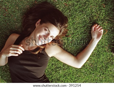 female model laying in grass - stock photo