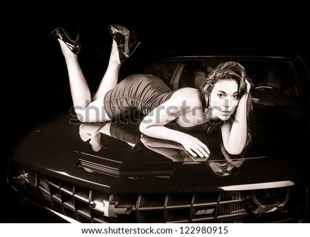 Female model laying on a car. - stock photo