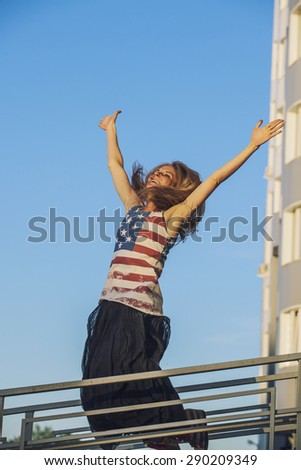 Female model on the background of blue sky in a t-shirt with the American flag