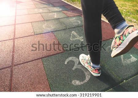 Female model playing hopscotch game outdoor. - stock photo