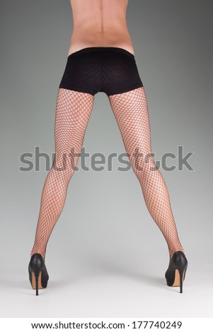 female model showing legs and waist posing wearing high heeled shoes and fish net stockings - stock photo