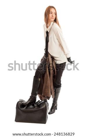 Female model stepping on black leather bag on white background - stock photo