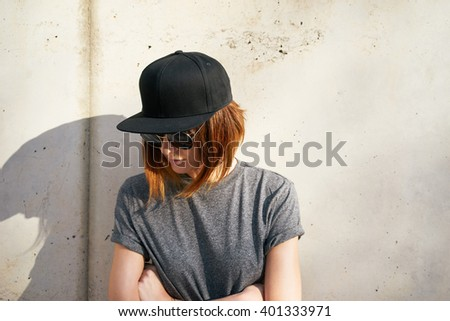 Female model wearing a black blank cap and sunglasses looking away. Portrait of a young beautiful girl with cap - stock photo