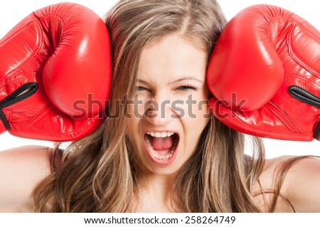 Female model wearing red boxing gloves screaming or shouting expressing madness or angry - stock photo