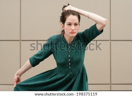 Female model with natural look posing outdoors with an iron background, wearing a green summer dress and grabbing her hair. - stock photo