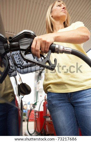 Female Motorist Filling Car With Diesel At Petrol Station - stock photo