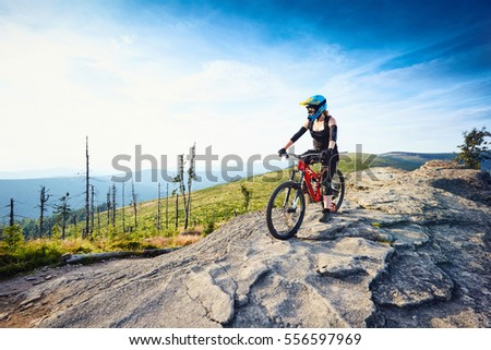 Female MTB mountain biker enjoys the view during sunny day in Mountains