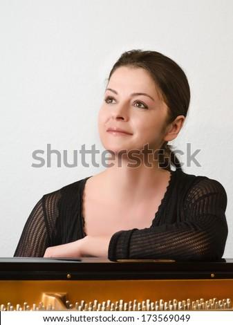 Female musician by the grand piano - stock photo