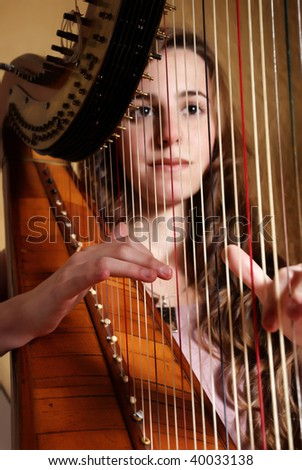 Female musician playing the harp - stock photo