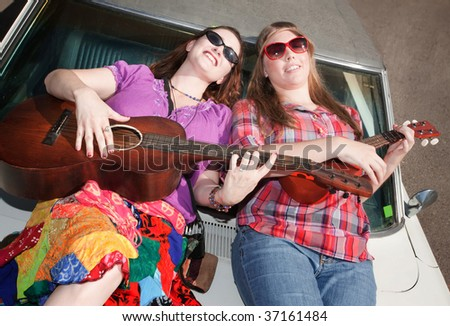 Female Musicians on an Old Car - stock photo