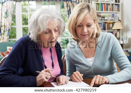 Female Neighbor Helping Senior Woman To Complete Form - stock photo