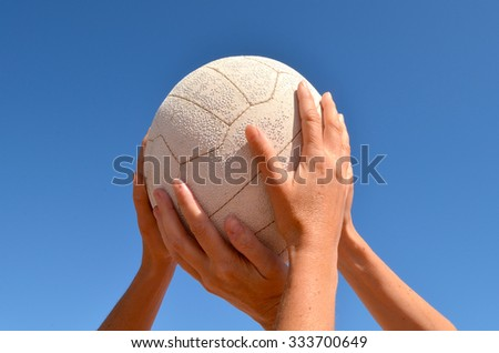 Female netball players competing for a netball above their heads on a beautiful blue sky day. - stock photo